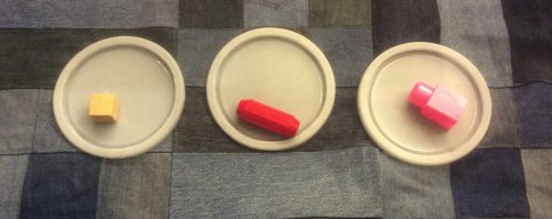 Three circular lids placed on a denim quilt background. Each lid has a different object on it. A block, a red cylinder magnet toy, and a pink megablock.