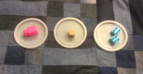 3 circular lids placed on a denim quilt background. Each lid has a different object on it. A pink mega block, a small wood cube block, and a blue duple block. The lid with duplo blocks has two identical blocks on it.